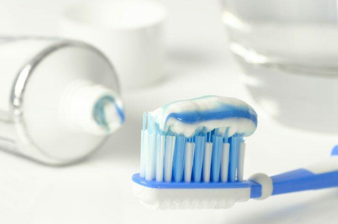 Blue and white toothbrush sits next to a tube of toothpaste and a glass of water illustrating the most common of uses for toothpaste.