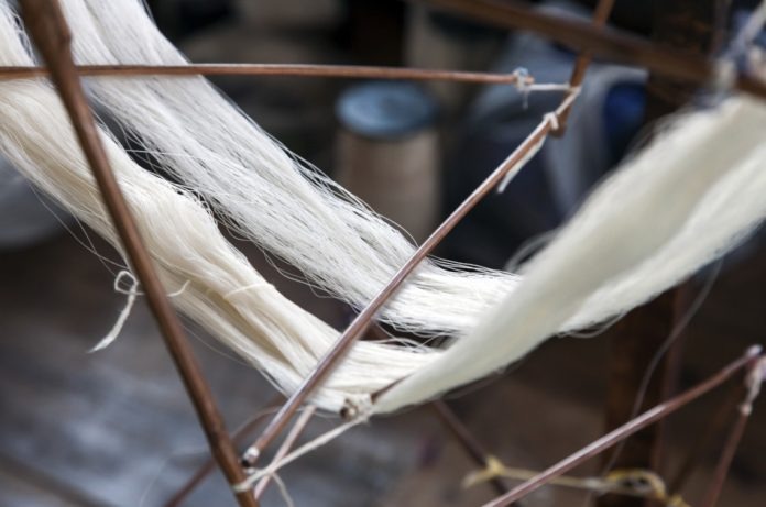 Silk weaving – Newly spun silk on a spindle at a silk factory in Inle Lake, Myanmar.