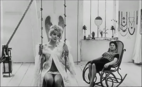 lady sits on swing in apartment from film still of Agnes Varda film Cleo 5-7
