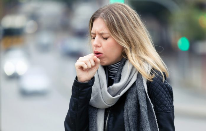 A blonde woman with a dark coat and gray scarf coughs while standing on a sidewalk.