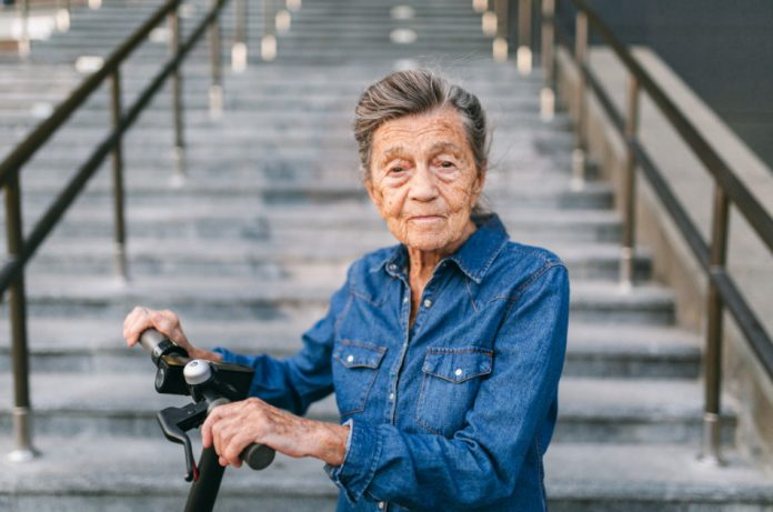 Elderly woman with blue denim shirt stands with an electric scooter at the base of some concrete steps.