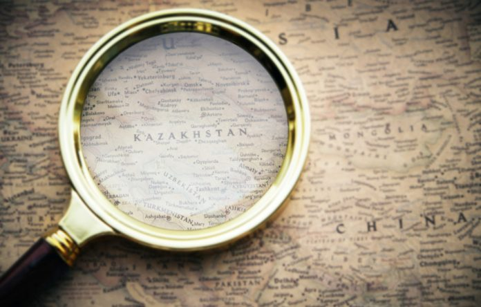 An old map with a magnifying glass sitting on top of Kazakhstan.