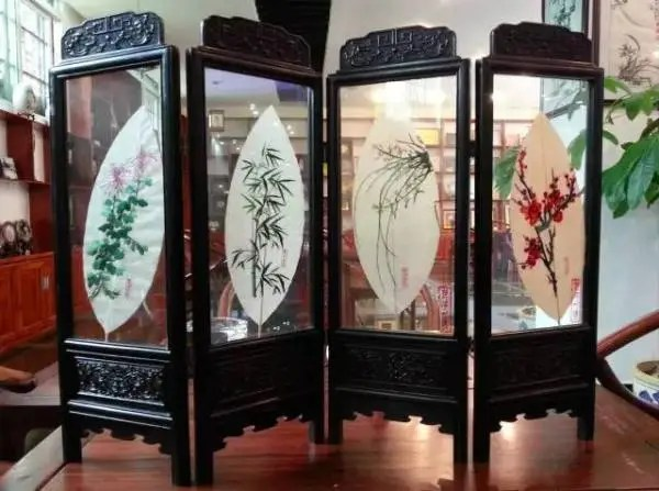 Finished leaf embroidery pieces, illustrating traditional themes of bamboo and chrysanthemum.