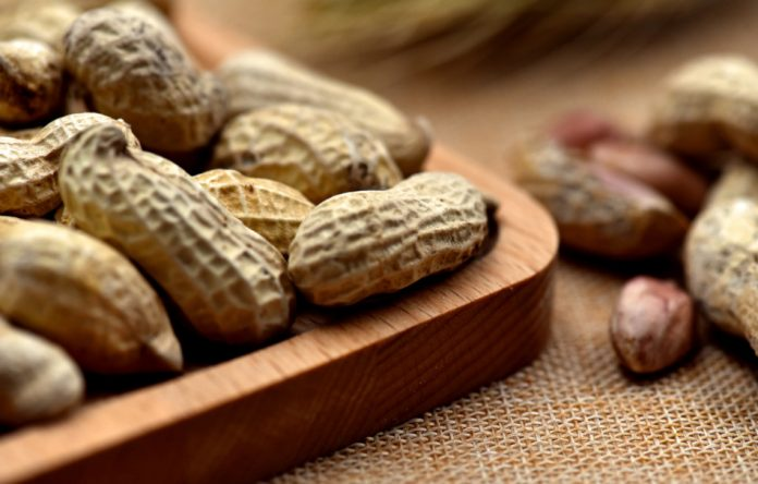 Peanuts in the shell sit on a wooden board on top of a placemat.
