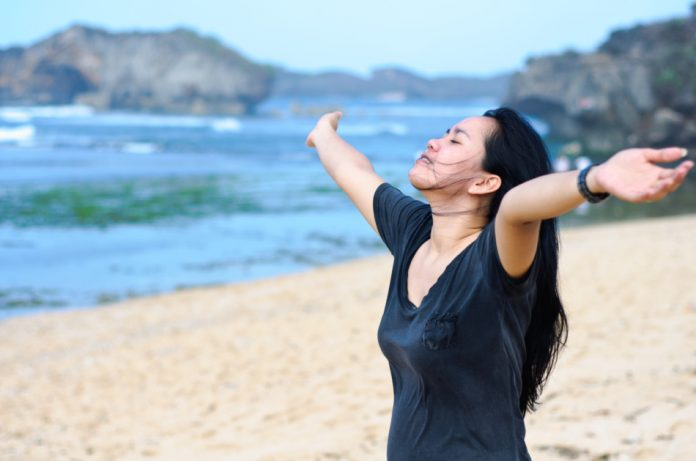 Pretty young Asian woman with her eyes closed, face turned up to the sun, hands raised, and arms outstretched standing on a beach.