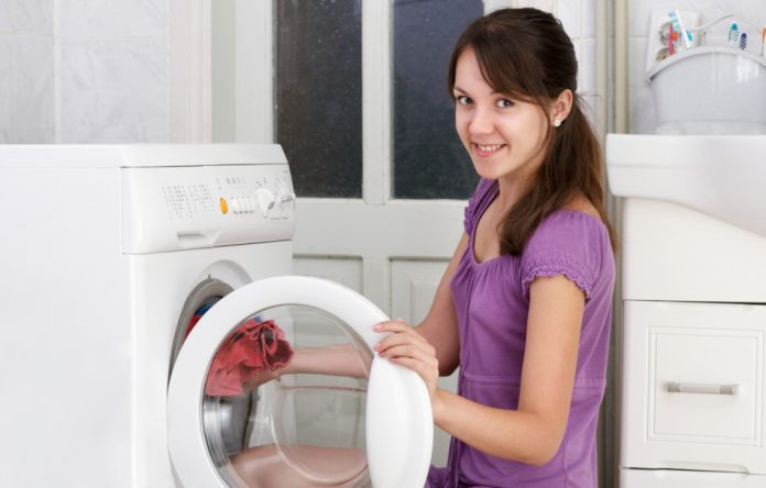 A young woman puts clothes in a front-load washing machine.