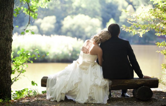 Couple in their wedding clothes sit together on a bench made from a log with the bride leaning her head on the groom's shoulder as they look out over a lake.