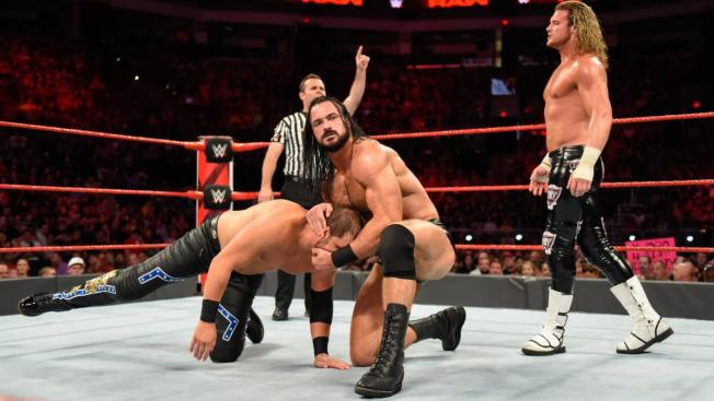 Drew McIntyre hold Curtis Axel by the head while Dolph Ziggler looks on
