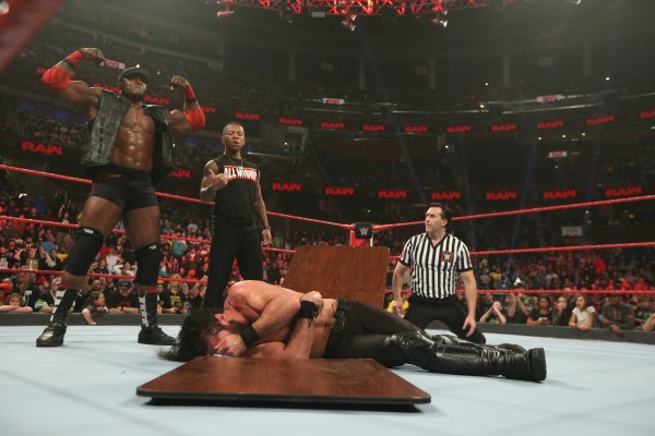 Bobby Lashey and Lio Rush stand over Rollins after they put him through a table