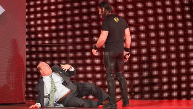 Seth Rollins stands over Paul Heyman