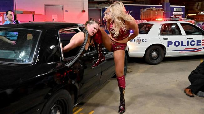 Charlotte Flair knees Ronda Rousey's head into the side of a car