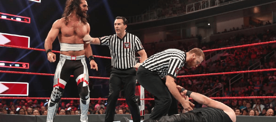 A ref holds Seth Rollins back from Sami Zayn and Kevin Owens