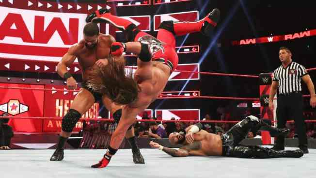 AJ Styles kicks Robert Roode in the head with Ricochet in the background
