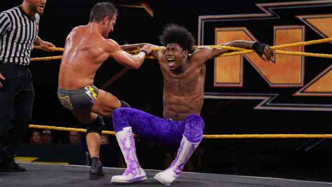 Roderick Strong with Velveteen Dream trapped in the ropes