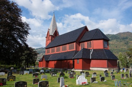 Bright red Sogndal's Stedje church with graveyard.