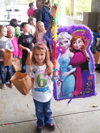 Miley with her sack of candy and the Frozen Pinata