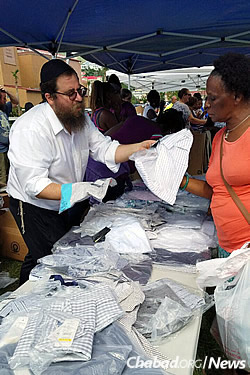 Rabbi Asher Federman, co-director of Chabad Lubavitch of the Virgin Islands, helps a woman locate an article of clothing.