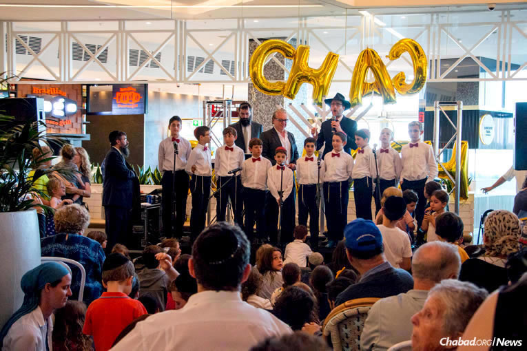 Chabad Rabbi Levi Wolf addressees the crowd at the menorah-lighting organized by The Central Synagogue at the Westfield Bondi Junction shopping center in Sydney, Australia, on Tuesday, Dec. 12, the first night of the eight-day holiday of Chanukah. (Photo: Alon Bar David)