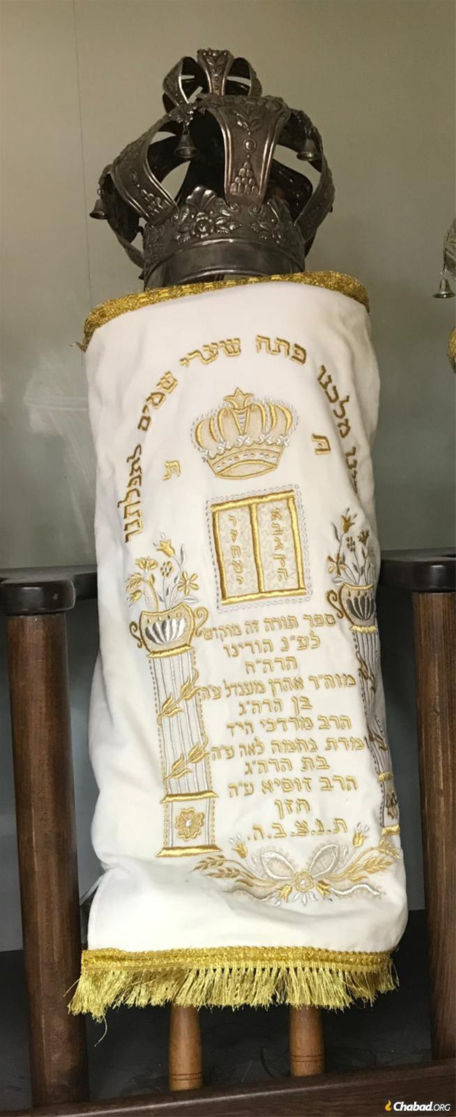 The Tula Torah in its white High Holiday mantle, dedicated to the memory of Rabbi Aharon and Nechamah Leah Chazan.