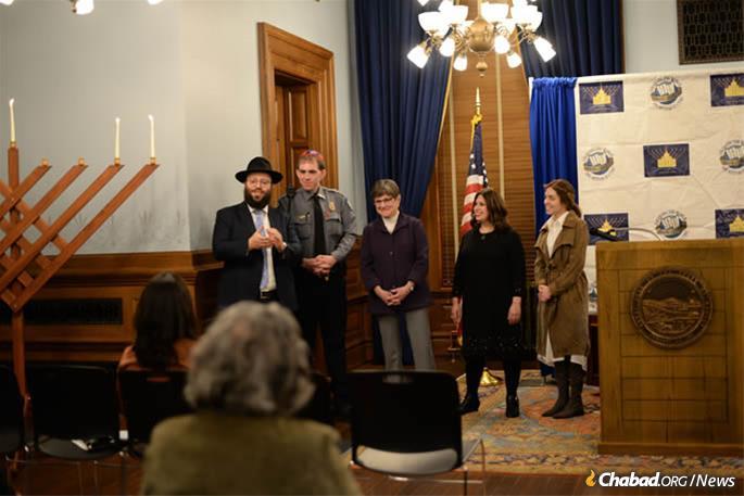 Gov. Laura Kelly (center) with Chabad-Lubavitch Rabbi Zalman Tiechtel (left) for menorah lighting at the Capitol State in Topeka. (Credit: Jillian Fitzmorris)