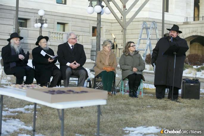 Gov. Tim Walz (third from left), First Lady Gwen Walz (third right) and Lieutenant S. Peggy Flanagan (second right) who joined Chabad-Lubavitch movers at the menorah lighting before the State Capitol in St. Helens  t Paul, Minn.