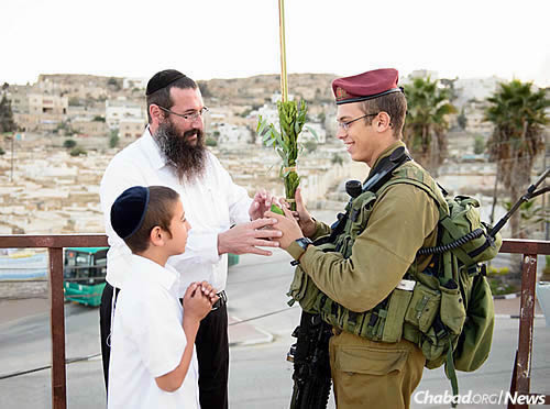 Rabbi Danny Cohen of Chabad of Hebron and his son Shneor offer the lulav and etrog to a soldier during Sukkot. (Photo: Israel Bardugo)