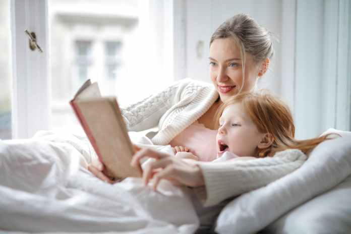 mother and daughter reading book with interest in bed
