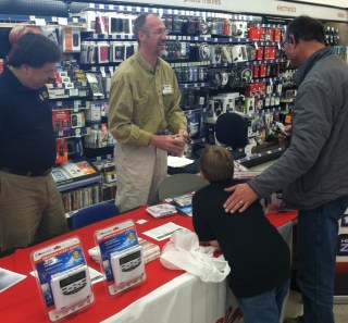 Photo of N9TB and KC9MUT programming weather radios at a Walgreens store