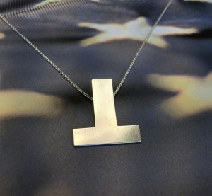 A silver metal inverted T charm suspended from a silver chain on a blue background with white stars reminiscent of the US flag.