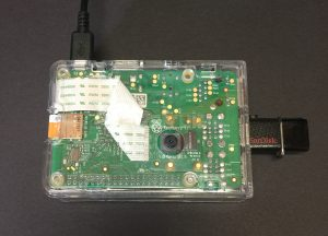 A clear plastic box containing a circuit board and camera. A power cable is attached to the top and a removable USB drive to the side.