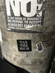 "A sticker displaying ""TAX THE RICH"" on a lamp post along with other stickers."