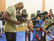 Volunteer Martin observes Harrison as he adjusts his brakes