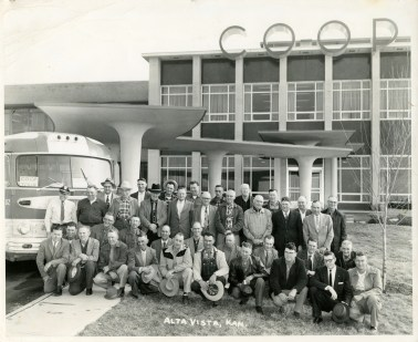 From the Bat Nelson Collection, this is a view of a group from the Alta Vista Coop on a trip to the Co-op Office Building in Kansas City, dated January 30, 1958. Front row, left to right: Vernon Zeckser, Oral Weeks, Homer Roberts, Walter Kraus, Vernon Richter, Clyde Thomas, Albert Meinhardt, Theodore Jones, Victor Zimmerman, and Virgil Bryant. Second row, left to right Aaron Unruh, Harlow Crowell, O.H. Swenson, George Eberle, Roy Carlton, Wayne Horne, Dale Fechner, Emmett Furney, and Walter Rutledge. Third row, left to right, Chas. Wrenn, Carl Ziegenhirt, Purley Horne, Bert Sisson, Arthur Kahle, T.W. Hodge, W.R. Zimmerman, Henry Andres, M.W. Andres, and Walter Swartz. Fourth row, left to right, Roy Reed, John Litke, Maurice Cashman Wallace Cripps, Dan Cashman, William Reineke, Benjamin Pape, C.E. Ensiminger, and Ed Newmeyer.