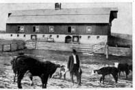 Henry Sump, stands in the foreground with his barn visible in the background. Sump had the barn built in 1905.