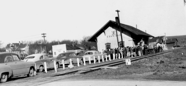 A crowd waits for a train at the Eskridge ATSF depot in this early 1950s photograph. Notice the Eskridge Star Grange to the left of the depot in this view and the Coffee house at the far left.
