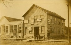 Henry Schmitz, right, stands beside the building which was the first Wabaunsee County Courthouse. To the left of the courthouse building is the E. Meyer store. When this view was taken around 1890, the building housed a saloon. The three boys in front of the doorway are unidentified.