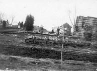 The Seymour residence in East Eskridge was demolished by the storm. Several men are seen here perched on the side of an exposed wall while others view the rubble.