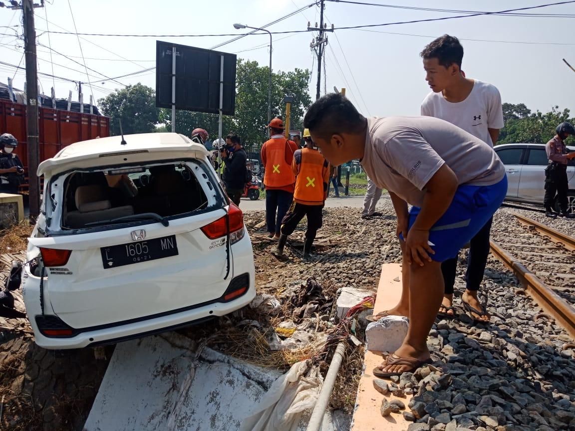 Kondisi mobil reusak berat dan hampir masuk selokan saat sejumlah warga melihat kelokasi. (wacananews.co.id/tyo)
