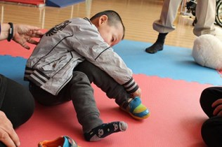 Young boy sits, leaning to look at his shoe, on red and blue checkered mat at orphanage during WACAP Visit to China 2016