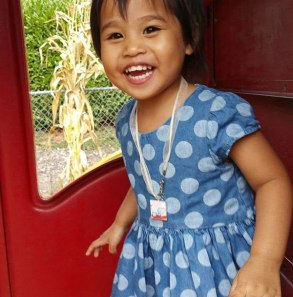 child plays and smiles happily against red door with window