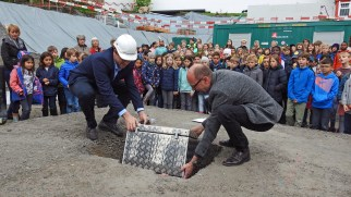 Lucien Salpeter und Sacha Mannhart lassen die Zeitkapsel vorsichtig in die Grube gleiten, mit Spannung von den Kindern und Gästen beobachtet.
