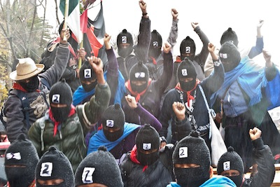 Zapatistas from contingent number 29 raised their fists atop the platform in downtown San Cristóbal de las Casas on December 21, 2012. (WNV/Marta Molina)