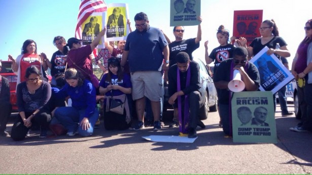 Members of Puente Arizona pray together as they put their bodies on the line to block access to a Trump rally. (Twitter / Puente Arizona)