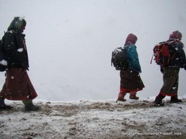 women walking under snow at rohtang pass, india