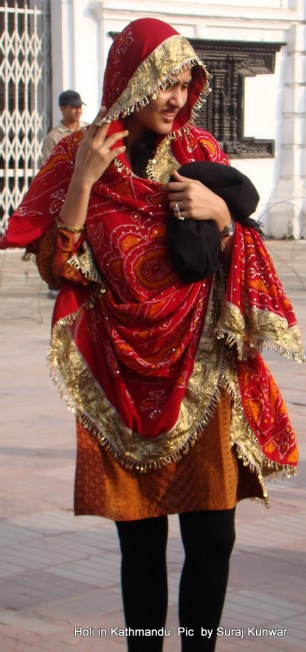 A Marwari girl looks for her friends after she performs pooja at the Cheer as part of Holi celebrations by her community
