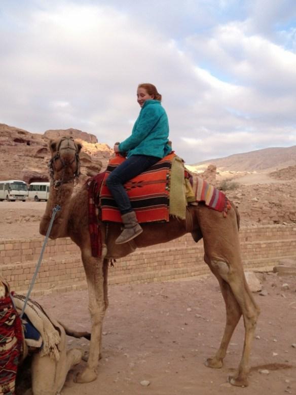 Calla discovers just how tall a camel is at Petra, Jordan.