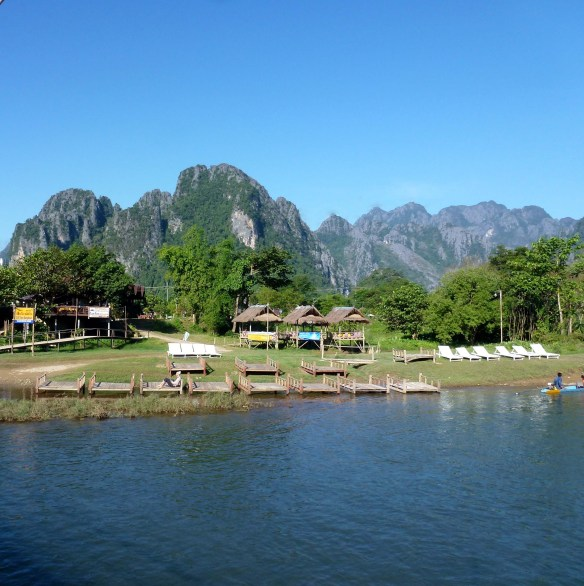 Vang Vieng Laos -the other side of the river.  Traveling on the VIP Bus from Luang Prabang to Vang Vieng Laos, what is it like? Gorgeous scenery, fast service and a video to share it all, even landslides! Read more on WagonersAbroad.com