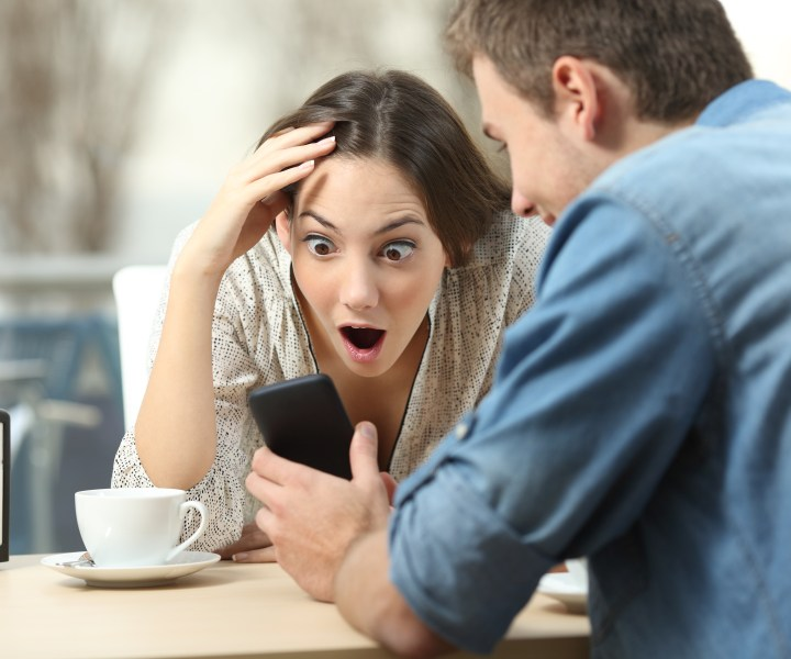 Surprised couple meeting in a coffee shop watching media content in a smart phone