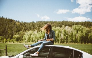girl sitting on car