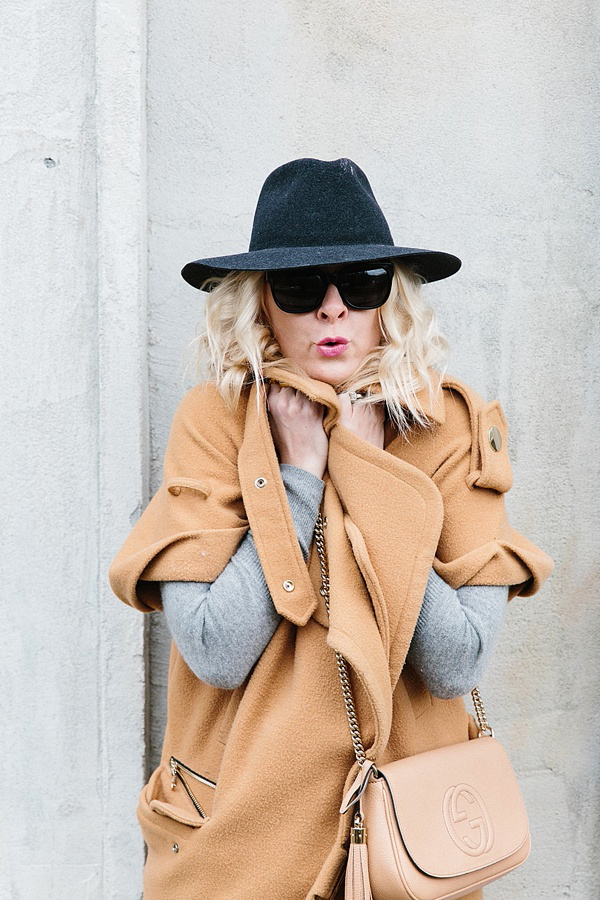 Camel coat and black wool hat